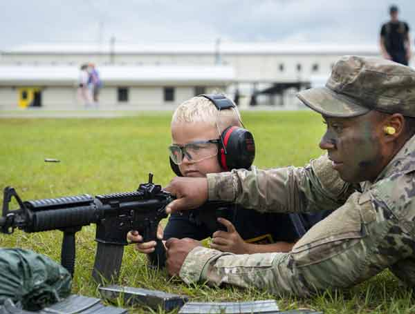 A Soldier helps a young recruit fire a rifle during the 6th Ranger Training Battalion's open house event May 11 at Eglin Air Force Base, Fla. The event was a chance for the public to learn how Rangers train and operate.