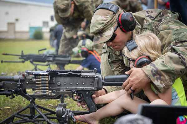 A Soldier helps a young recruit fire a machine gun during the 6th Ranger Training Battalion's open house