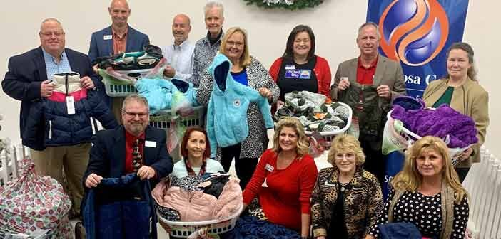 okaloosa gas employees pose with coats