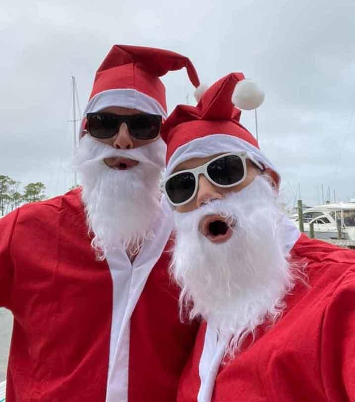 santas pose at Bluewater Bay Marina Santa Paddleboard Parade